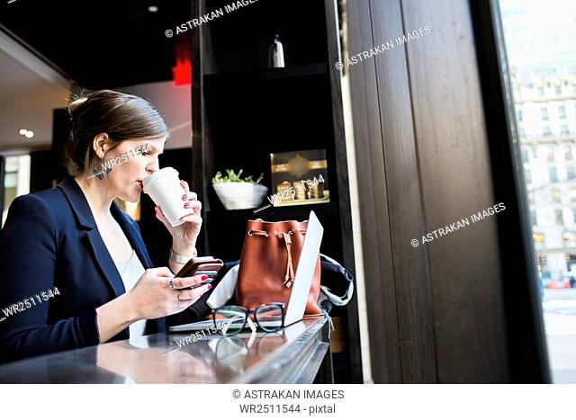 Businesswoman drinking coffee while using technologies at coffee shop
