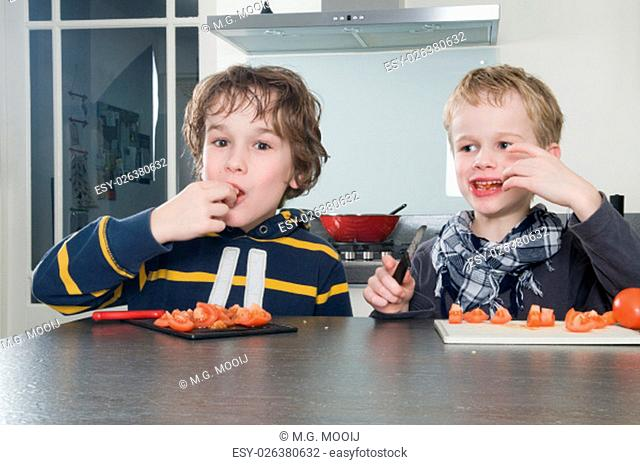 Two boys tasting the just cutted tomatos, used for cooking