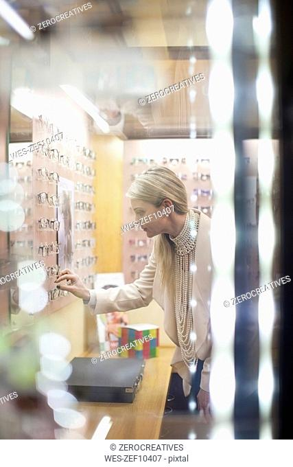 Blond woman selecting new glasses in opticians shop