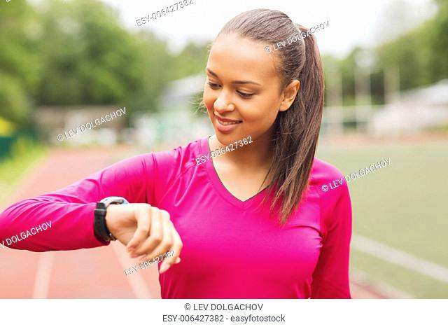 fitness, sport, training, technology and lifestyle concept - smiling african american woman with heart-rate watch on track outdoors