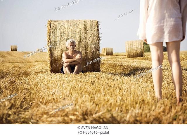 A naked man reclining against a hay bale facing a the back of a woman