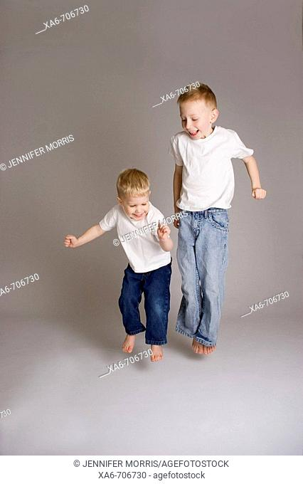 Two blond haired little boyes, aged 6 and 3 years, wearing white t-shirts and blue jeans, smiling and jumping. Studio lighting, grey background