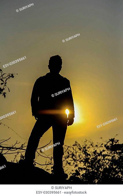 Man standing looking evening sun