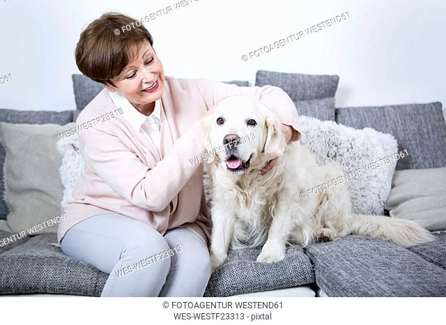 Senior woman sitting on couch with her dog