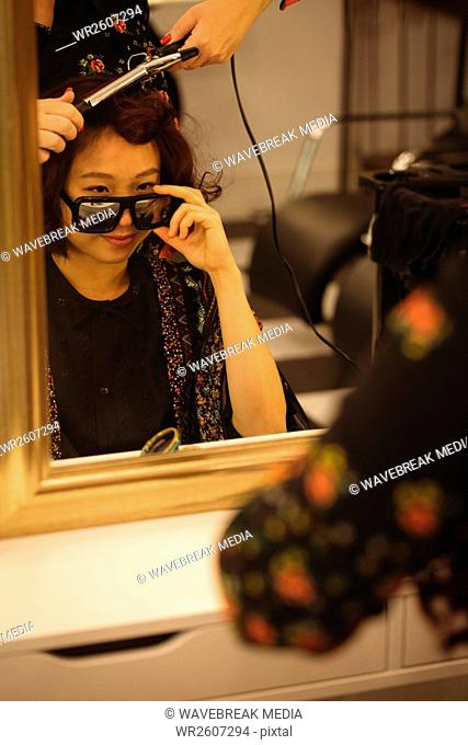 Stylish woman looking over sunglasses while getting her hair done