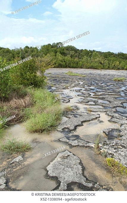 The puddled shore of Mckinney Falls in Texas