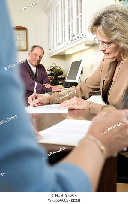 Woman writing on papers with man sitting in the background