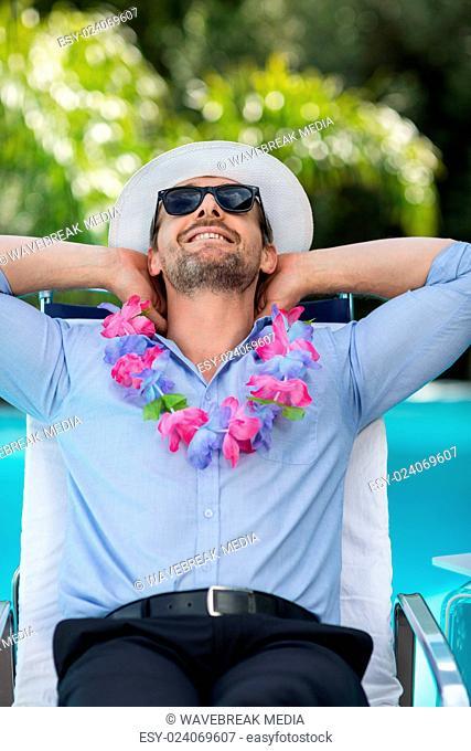 Smart man wearing garland while relaxing in sun lounger