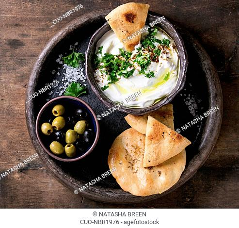 labneh middle eastern lebanese cream cheese dip with olive oil, salt, herbs served with olives, traditional pita bread on terracotta plate over dark texture...