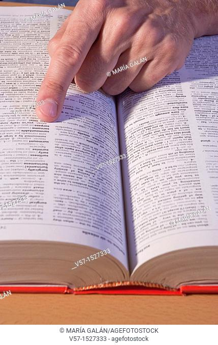 Man's hand looking up a word in the dictionary. Close view