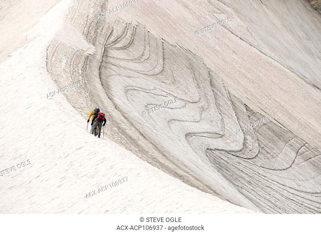 Two climbers ascend a snow slope while heading up Mt. Strom in Assiniboine Provincial Park, BC
