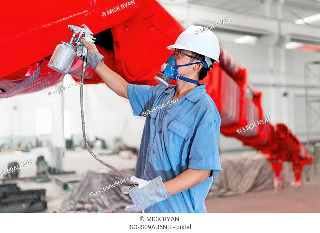 Male worker spray painting a crane arm red in factory workshop, China