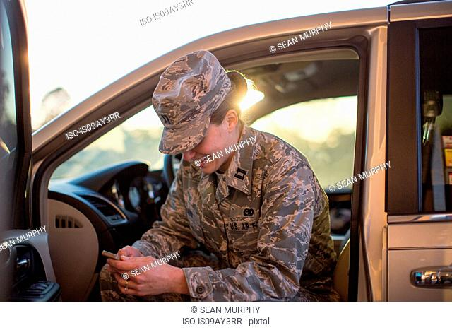 Female soldier sitting in car texting on smartphone at air force military base