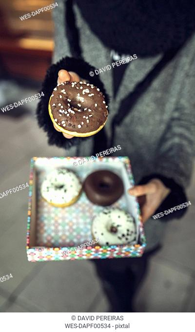 Woman holding doughnut with chocolate icing, partial view