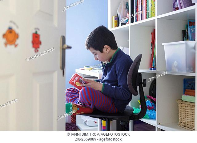 Schoolboy,7 years old,reading a book in his room