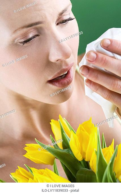 Close-up of a young woman sneezing