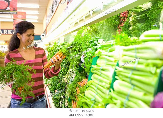 Woman choosing carrots in grocery store