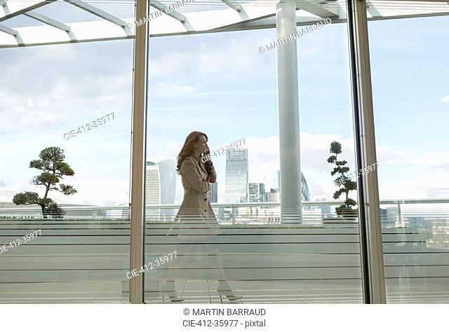 Businesswoman talking on cell phone on urban balcony with city view