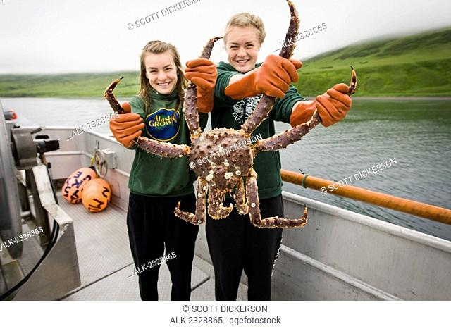 Commercial fishing deckhands, Claire and Emma Teal Laukitis, hold up a live Bristol Bay red king crab on a boat in Isanotski Strait near False Pass, Alaska