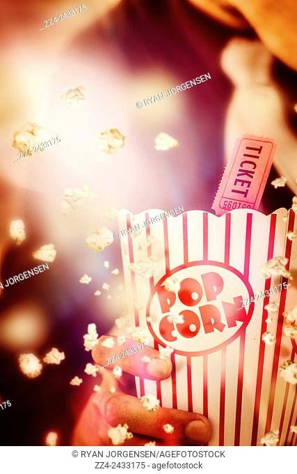 Artistic still-life picture on popcorn exploding with blast of action packed motion outside of striped retro packaging. Vintage film and cinema