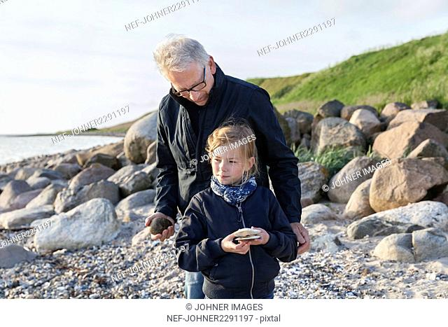 Grandfather with granddaughter on beach