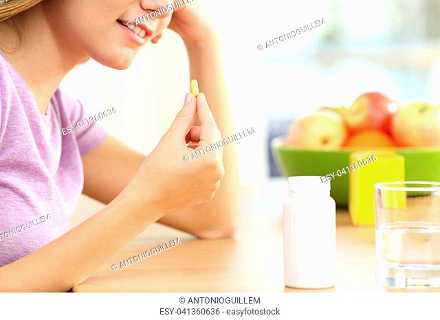 Close up of a girl hand taking vitamin pill on a table at home with a window in the background and a colorful decoration