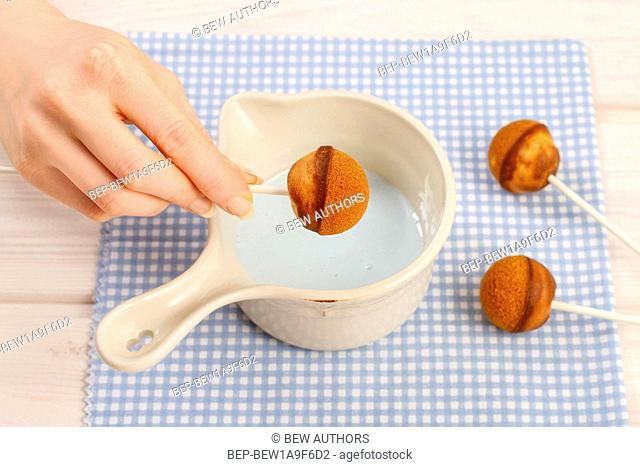 Decorating cake pops with blue icing. Party dessert