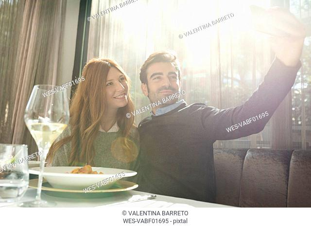 Smiling couple taking a selfie in a restaurant