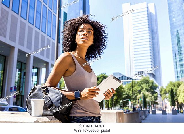Germany, Frankfurt, portrait of young woman with travelling bag, tablet and coffee to go in the city