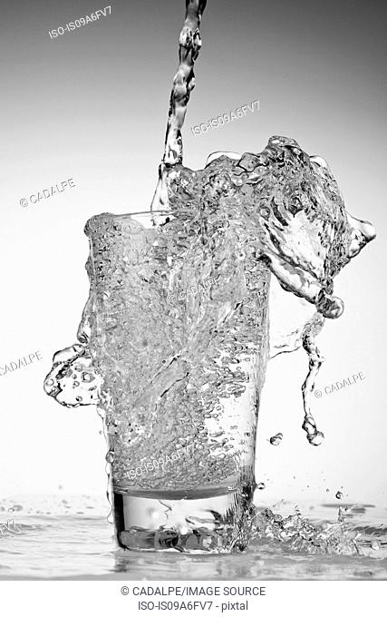 Water being poured into drinking glass and overflowing