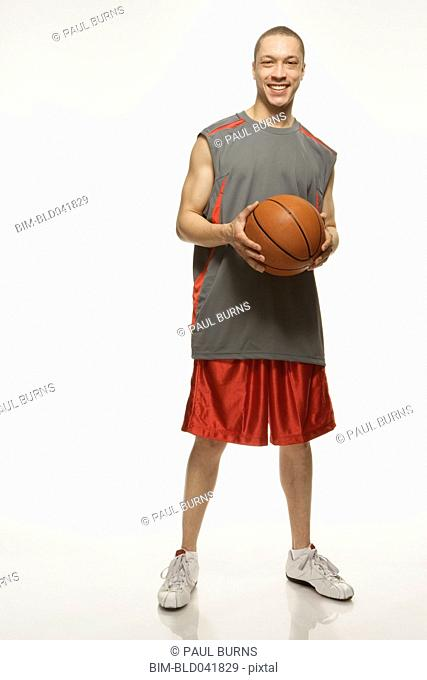 Mixed Race man holding basketball