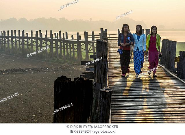 Girls with tanaka on their faces on a teak bridge, U Bein Bridge over Taungthaman Lake, in the morning light, Amarapura, Mandalay Division, Myanmar