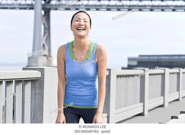 Female runner taking break on bridge, San Francisco, California