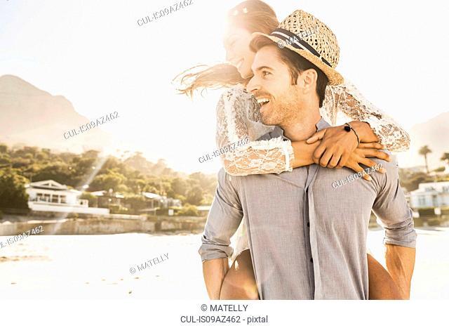 Man giving girlfriend a piggy back on sunlit beach, Cape Town, South Africa