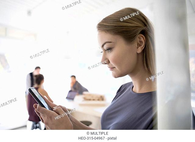 Female architect texting with cell phone in office