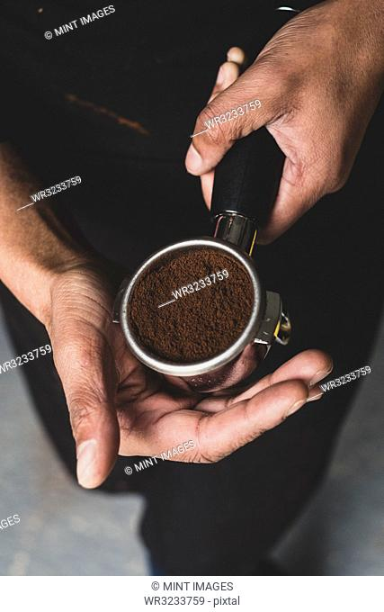 High angle close up of person holding espresso machine portafilter with ground espresso