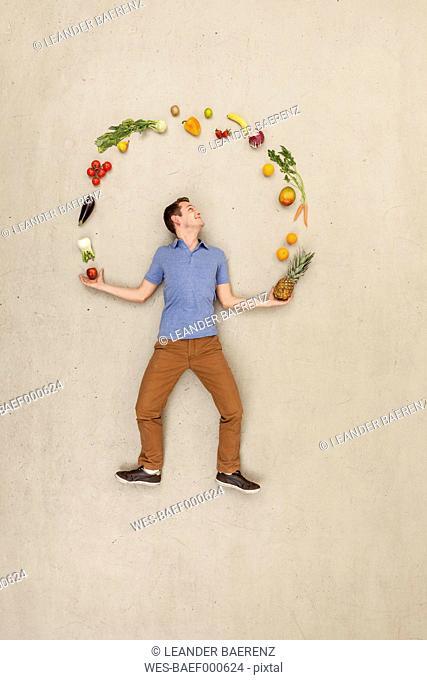 Man juggling food against beige background
