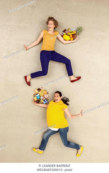 Women with food against beige background
