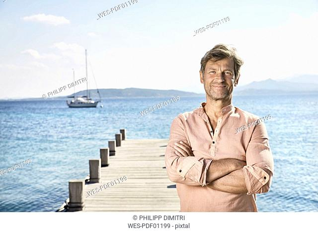 Portrait of smiling mature man standing on jetty