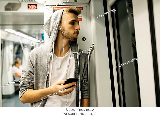 Young man using smartphone in metro