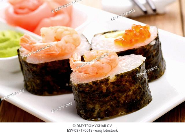 Mixed sushi set on a white plate with wasabi and ginger
