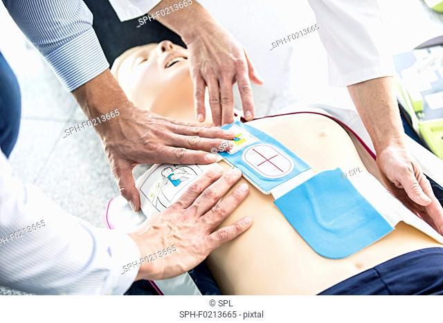 First-aider placing defibrillator pads