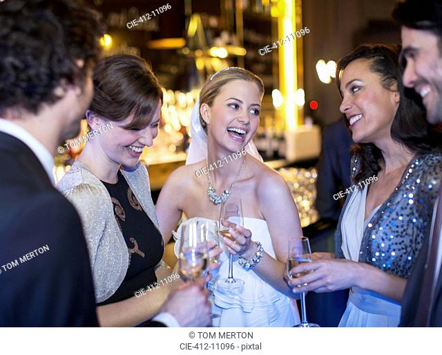Happy bride drinking champagne with friends at wedding reception