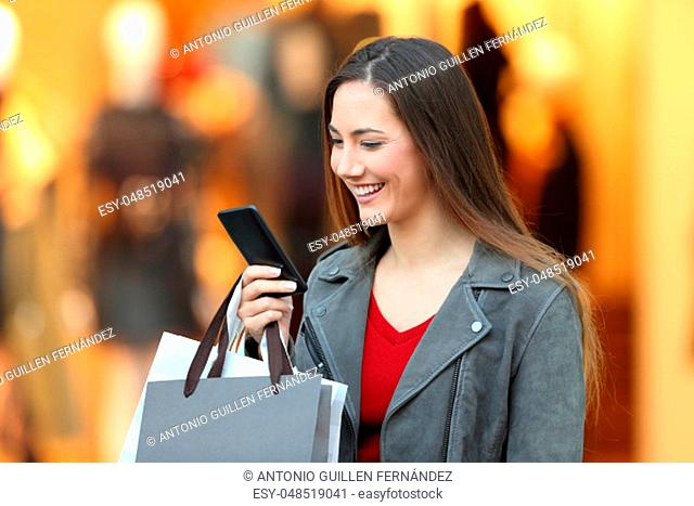 Portrait of a fashion shopper using a smart phone walking in a commercial centre