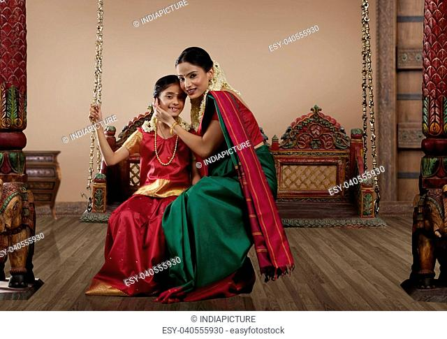 Portrait of a South Indian woman sitting with her daughter on a jhula