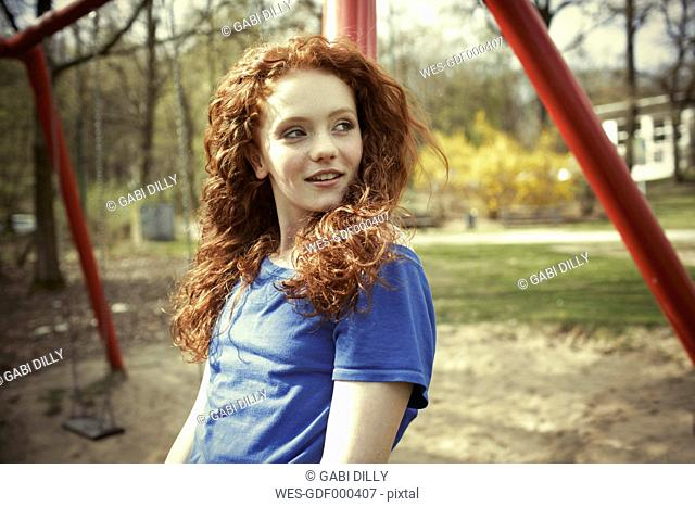 Portrait of smiling girl with curly red hair on a playground