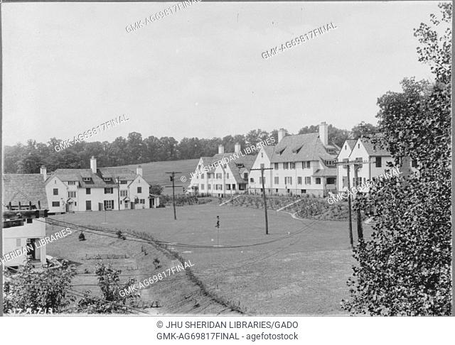 View of several homes alongside slight hill and grass field with telephone poles, homes are light-colored with many windows and trees around them, Baltimore