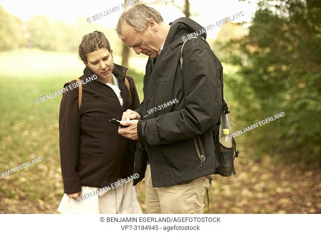 couple, age difference, outdoors, in park, generations, Grandfather, modern technology, smartphone, navigation, using smartphone, at Neuhofener Berg, Munich
