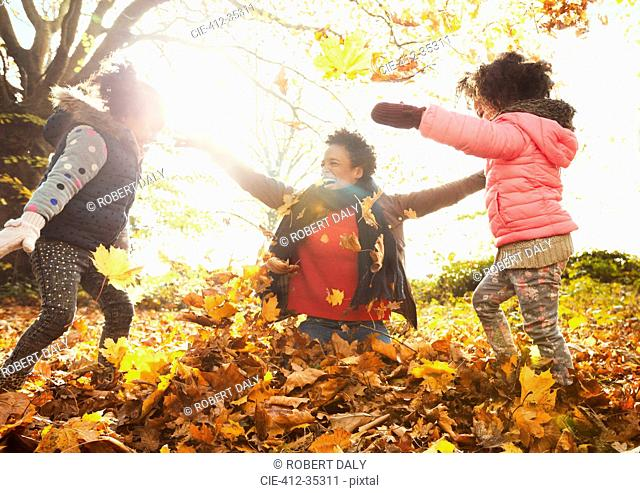 Playful mother and daughters throwing autumn leaves in sunny park