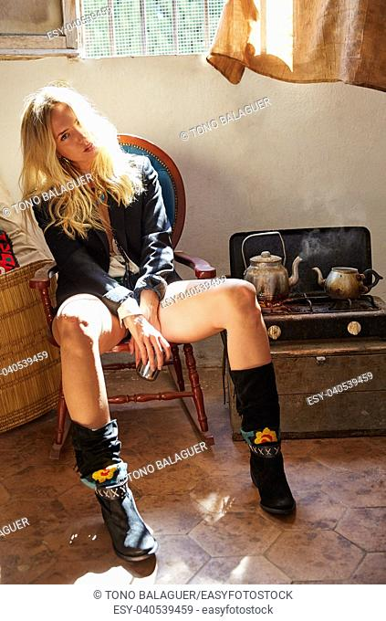 blond fashion girl drinking tea in a grunge indoor relaxed on vintage chair